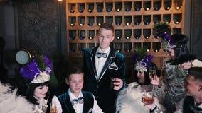Tematu przyjęcie mężczyzna w centre podnosi szkło napój w górę - ludzie w błyszczenia odzieżowym obsiadaniu za stołem - zdjęcie wideo