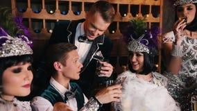 Tematu przyjęcie - młodzi ludzie w lśnić retro odzieżowego obsiadanie za stołem i pić alkohol zbiory