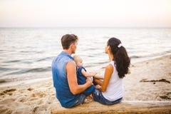 Tematu rodzinny weekend, plażowy wakacje z dzieckiem Młoda elegancka rodzina trzy tatów mama i córka siedzimy jeden rok z ich zdjęcie royalty free