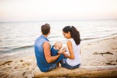 Tematu rodzinny weekend, plażowy wakacje z dzieckiem Młoda elegancka rodzina trzy tatów mama i córka siedzimy jeden rok z ich fotografia royalty free