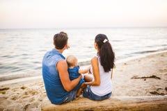 Tematu rodzinny weekend, plażowy wakacje z dzieckiem Młoda elegancka rodzina trzy tatów mama i córka siedzimy jeden rok z ich obrazy royalty free
