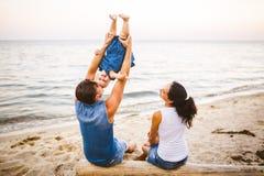 Tematu rodzinny weekend, plażowy wakacje z dzieckiem Młoda elegancka rodzina trzy tatów mama i córka siedzimy jeden rok z ich zdjęcie stock