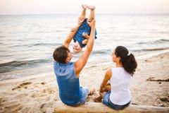 Tematu rodzinny weekend, plażowy wakacje z dzieckiem Młoda elegancka rodzina trzy tatów mama i córka siedzimy jeden rok z ich zdjęcia stock