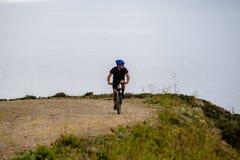 Tematurism och cykla på att cykla för berg grabben rider stigande på en stenig stenig väg mot bakgrunden av det medelhavs- Royaltyfri Foto