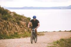 Tematurism och cykla på att cykla för berg grabben rider stigande på en stenig stenig väg mot bakgrunden av det medelhavs- Royaltyfri Bild