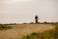 Tematurism och cykla på att cykla för berg grabben rider stigande på en stenig stenig väg mot bakgrunden av det medelhavs- Arkivfoton
