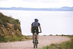 Tematurism och cykla på att cykla för berg ung grabb som ner rider på den hög hastigheten på stenigt, bergvägbakgrund medelhavs-  Arkivfoto