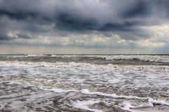 Tempête de mer La coupure de vagues sur la plage sablonneuse ciel tragique image libre de droits