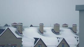 Tempête de neige contre les toits inclinés des maisons résidentielles dans la vidéo de casserole de l'hiver 4K banque de vidéos