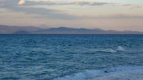 Tempête de soirée sur la mer bleue donnant sur le ciel et les montagnes Photo libre de droits