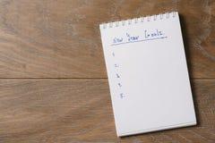 Tempate de las metas del Año Nuevo con la libreta en la tabla de madera Imagen de archivo libre de regalías