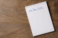 Tempate de las metas del Año Nuevo con la libreta en la tabla de madera Imagen de archivo