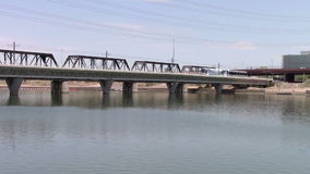 Tempe Town Lake. Tempe, Arizona, USA -  June 24, 2015:   Modern light rail trolley crosses the lake from the south shore to the north shore stock video
