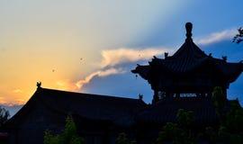 Tempel för traditionell kines silhouetted i solnedgången Royaltyfria Bilder