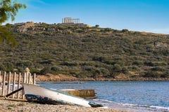 Tempel van Poseidon op de achtergrond en op de voorzijde van een oude vissersboot stock foto