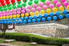 Tempelvägg och lyktorna - färgrika pappers- lyktor för dag arkivfoto