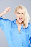 Temperamental woman raising her fist in anger. Temperamental attractive young blond woman raising her fist in anger and shouting at the camera in a fit of rage Stock Photography
