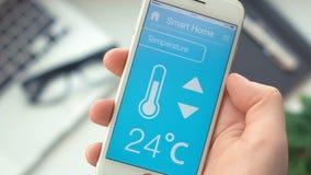 Temperatura cambiante en el hogar elegante app en el smartphone almacen de video