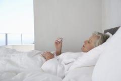 Temperatura da leitura da mulher do termômetro Fotografia de Stock