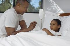 A temperatura de Checking Daughter do pai na cama Fotografia de Stock Royalty Free