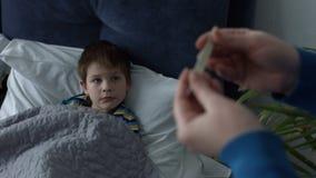 Temperatura de medición de la madre que cuida del muchacho enfermo almacen de metraje de vídeo