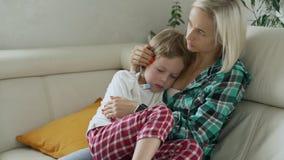 Temperatura di misurazione della madre del suo bambino malato a fondo Bambino malato con febbre alta che si trova al sofà a casa video d archivio