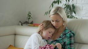Temperatura di misurazione della madre del suo bambino malato a fondo Bambino malato con febbre alta che si trova al sofà a casa stock footage