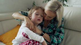 Temperatura di misurazione della madre del suo bambino malato a fondo Bambino malato con febbre alta che si trova al sofà a casa archivi video
