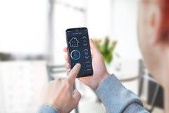 Temperatura y seguridad del hogar del control de la mujer de la oficina con el móvil moderno app foto de archivo