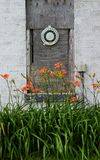 Temperature gauge on an old building. Old temperature gauge on and old building surrounded by flowers Royalty Free Stock Images