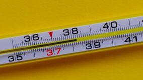 Temperature rising shown on a thermometer on a yellow background close-up.