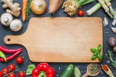 Tempere ervas e fundo do alimento dos vegetais e a placa de corte vazia Fotografia de Stock