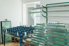 Tempered Window Glass in a PVC Factory. Sheets of Factory manufacturing tempered clear float glass panels cut to size Stock Images