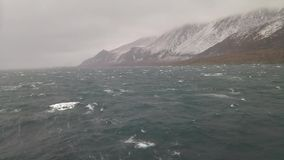 Tempest in the ocean near snowy mountains in Greenland stock footage