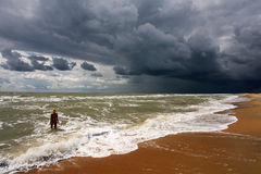 Tempest on a sandy beach. A girl bathes, and a storm begins on  a sea Stock Photos
