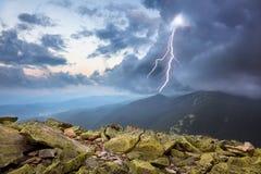 Tempestad de truenos con el aligeramiento y nubes dramáticas en montañas Imagenes de archivo
