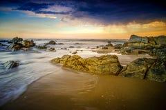 Tempestad de truenos que elabora cerveza sobre rocas grandes en la playa Imagen de archivo libre de regalías