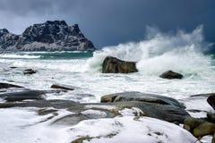 A tempestade acena na praia no arquipélago de Lofoten, Noruega no tempo de inverno, reflexão da água em Hamnoy fotos de stock royalty free