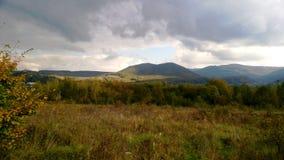 Tempestade sobre as montanhas na temporada de verão com o prado verde iluminado do Sun foto de stock royalty free