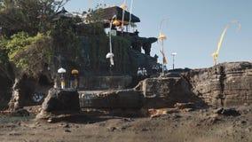 Tempio del lotto di Tanah con gli alberi su formazione rocciosa in oceano archivi video