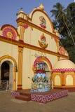 Tempio indù giallo luminoso con le statue dei di mitologia, contro il contesto delle palme verdi sotto il cielo blu immagine stock libera da diritti