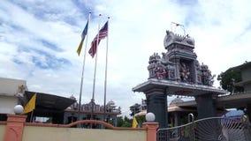 Tempio indù tradizionale esteriore con la bandiera d'ondeggiamento in Malesia video d archivio