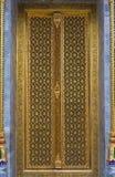 Tempio tailandese che scolpisce porta con la decorazione dorata fotografia stock