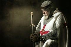 Templar knight. Praying in a dark background stock photo