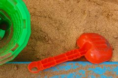 Children`s shovel, bucket and sand. A template consisting of sand in a sandbox, a children`s shovel, a bucket and sand Royalty Free Stock Photography