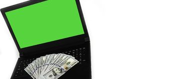 Template Copy Space with Laptop and Widespread of Money. Laptop or notebook with widespread of cash money isolated on white background with clean blank green royalty free stock photography