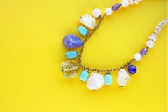 Template with copy space by top view closeup macro photo of a necklace of semi-precious stones on yellow paper stock photography