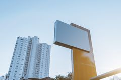 Template of empty metal informational city banner. Mock-up of a blank horizontal white advertising billboard with residential high-rise behind; the template of Stock Image