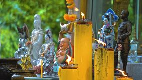 Temple buddha under the trees. Buddhism in Asia. candles and flowers. place of religious worship of believers.  stock video