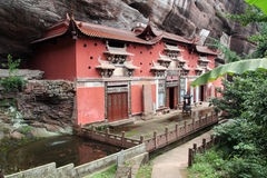 Temple building leaning against a vertical rock in Qiyun Taoist Stock Photography